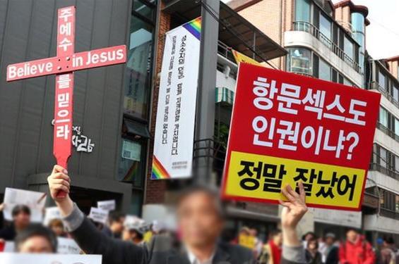 항문섹스도 인권이냐? 정말 잘났어. 라고 쓰인 피켓을 들고 있는 시위자.