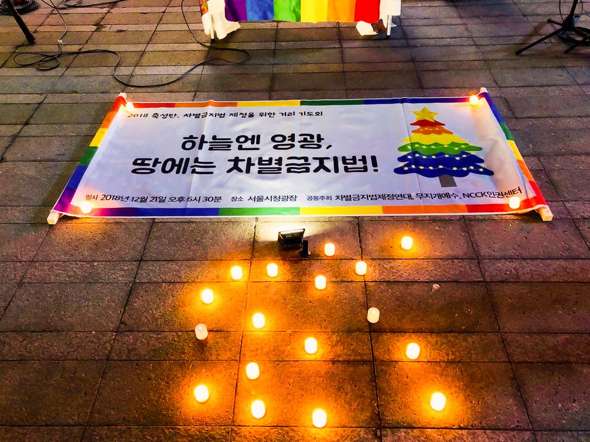 2018년 '축성탄, 차별금지법 제정을 위한 거리 기도회'의 사진. 하늘엔 영광, 땅에는 차별금지법이라고 쓰인 현수막이 촛불 가운데 놓여있다.