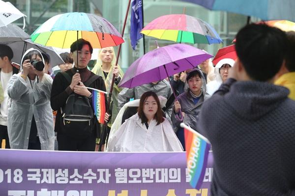 행사 참여자들이 빗속을 걷고 있다.